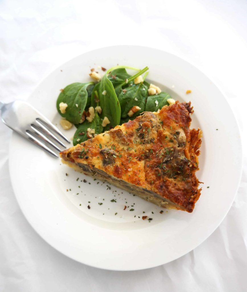 top view of quiche on plate with side salad and fork