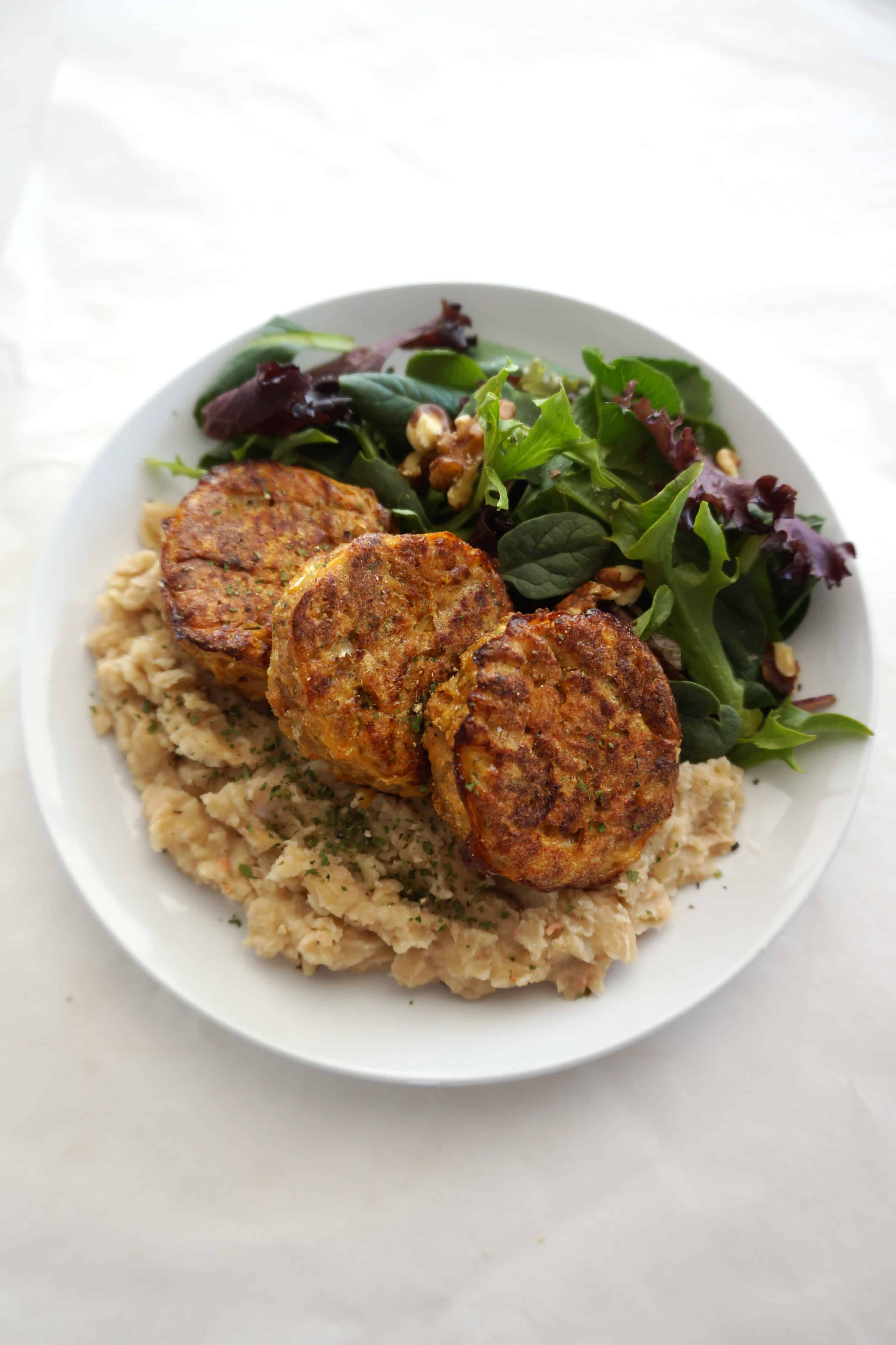 Salmon Patties on a plate with white bean mash and side salad