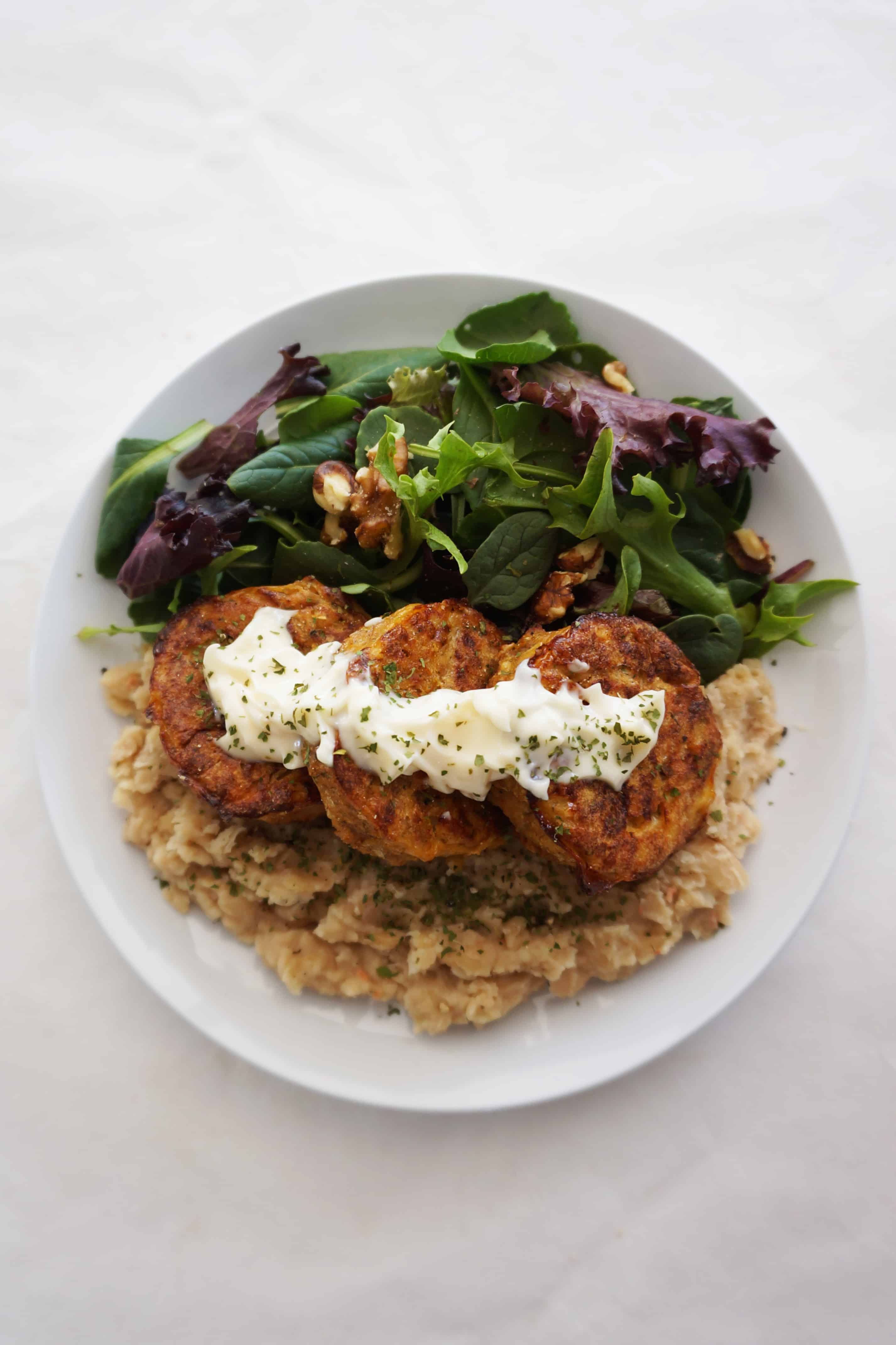 salmon patties on a plate with mayonnaise over the top accompanied by white bean mash and salad