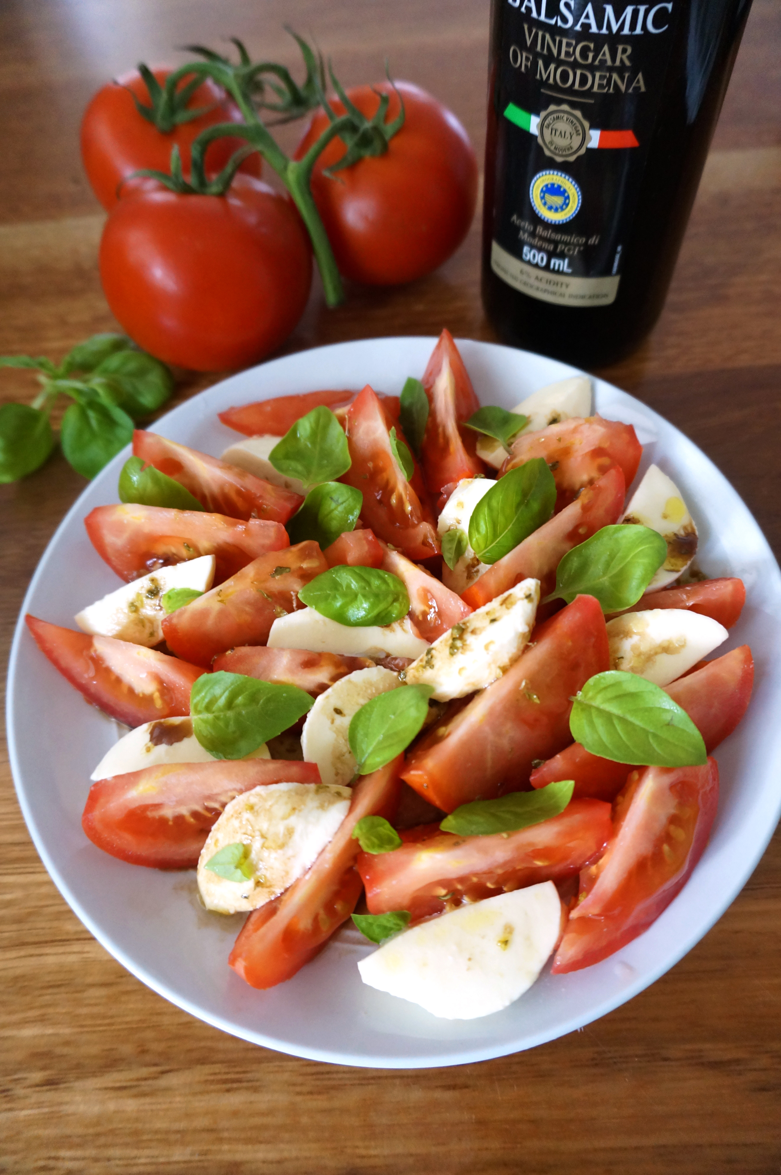 Tomatoes, basil leaves and balsamic vinegar behind a plate of bocconcini salad