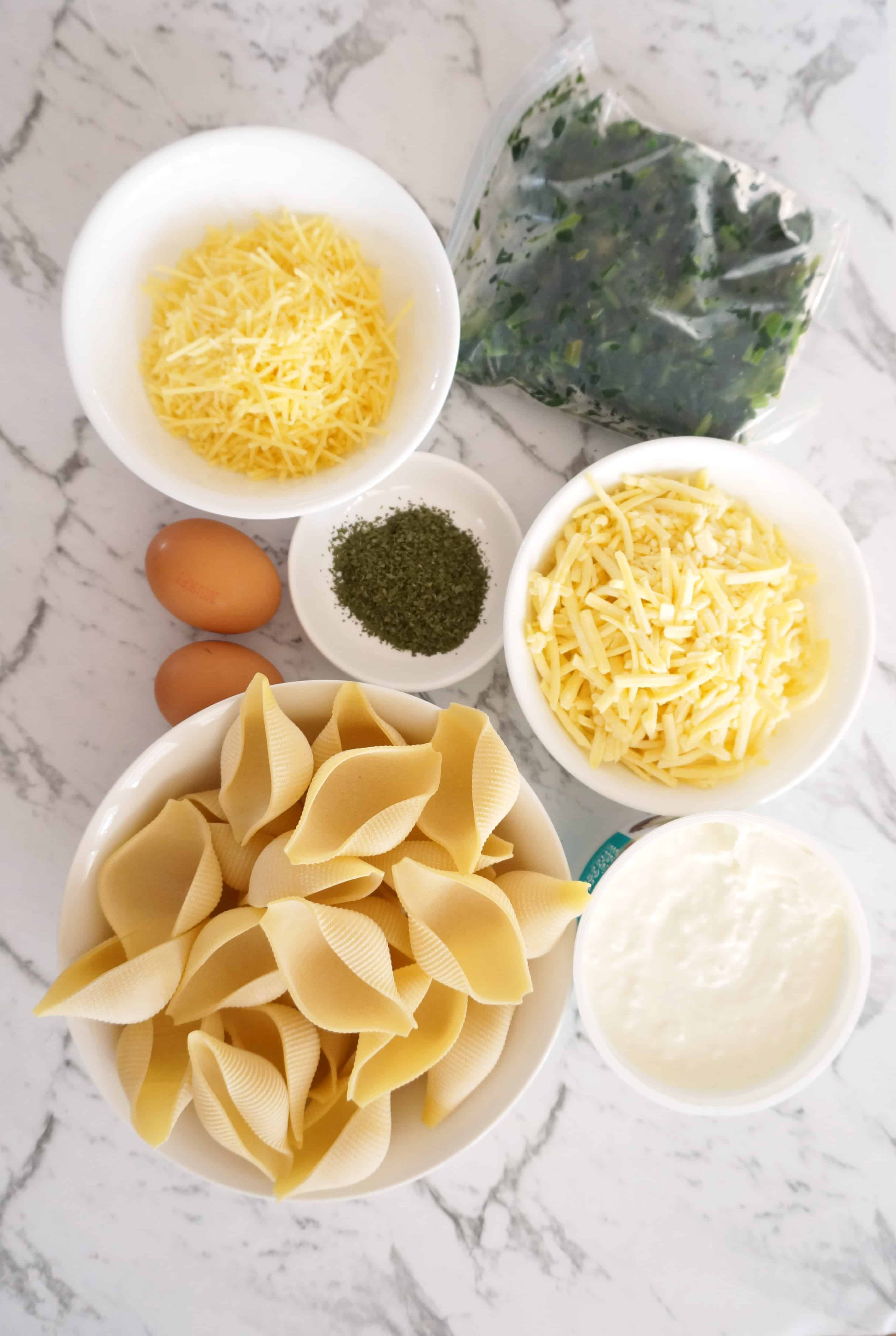 Ingredients for Stuffed Conchiglioni- grated parmesan, frozen spinach, eggs, dried parsley, cottage cheese, grated cheddar cheese, conchiglioni pasta shells