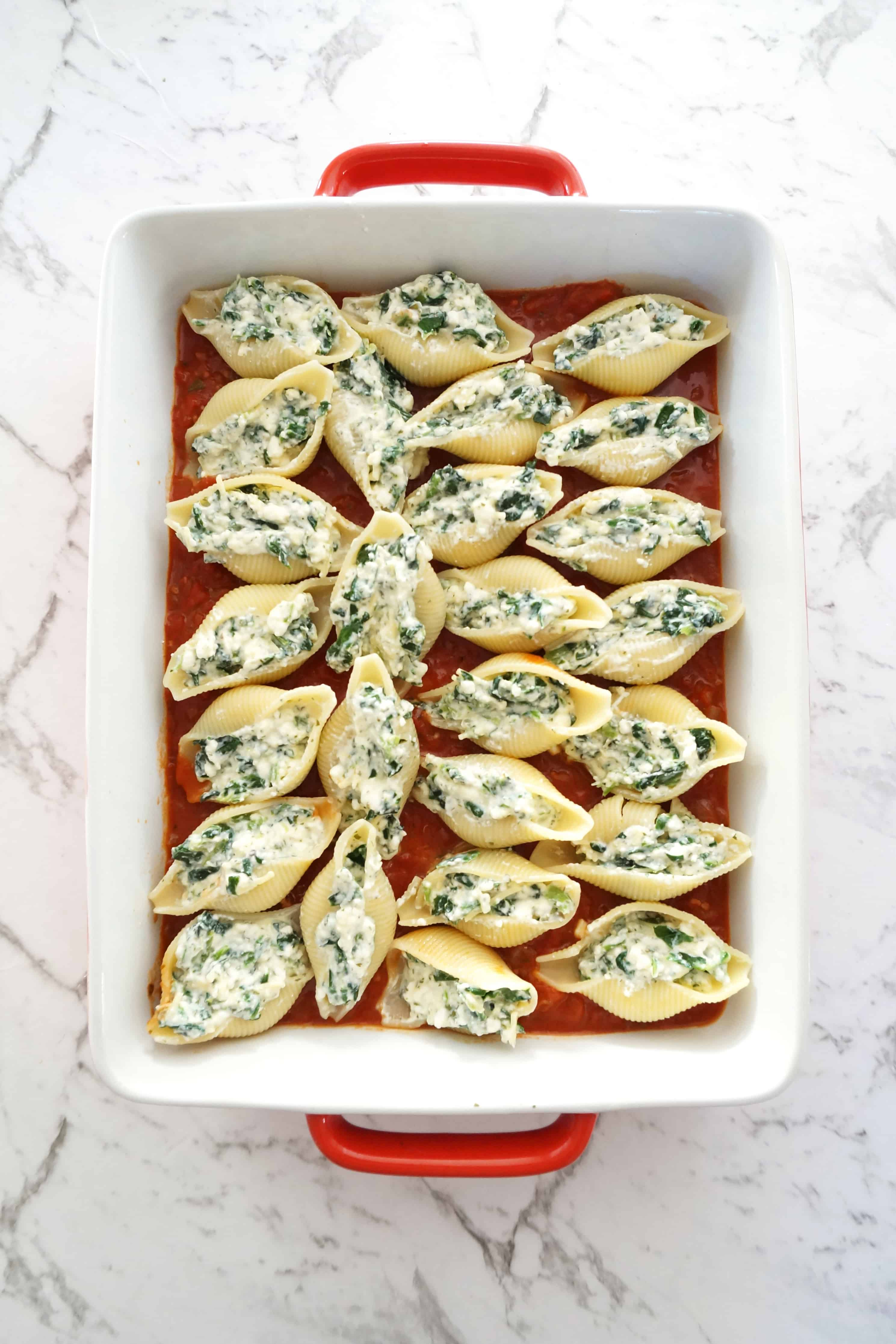 Unbaked spinach and cheese stuffed conchiglioni pasta shells in a red baking dish