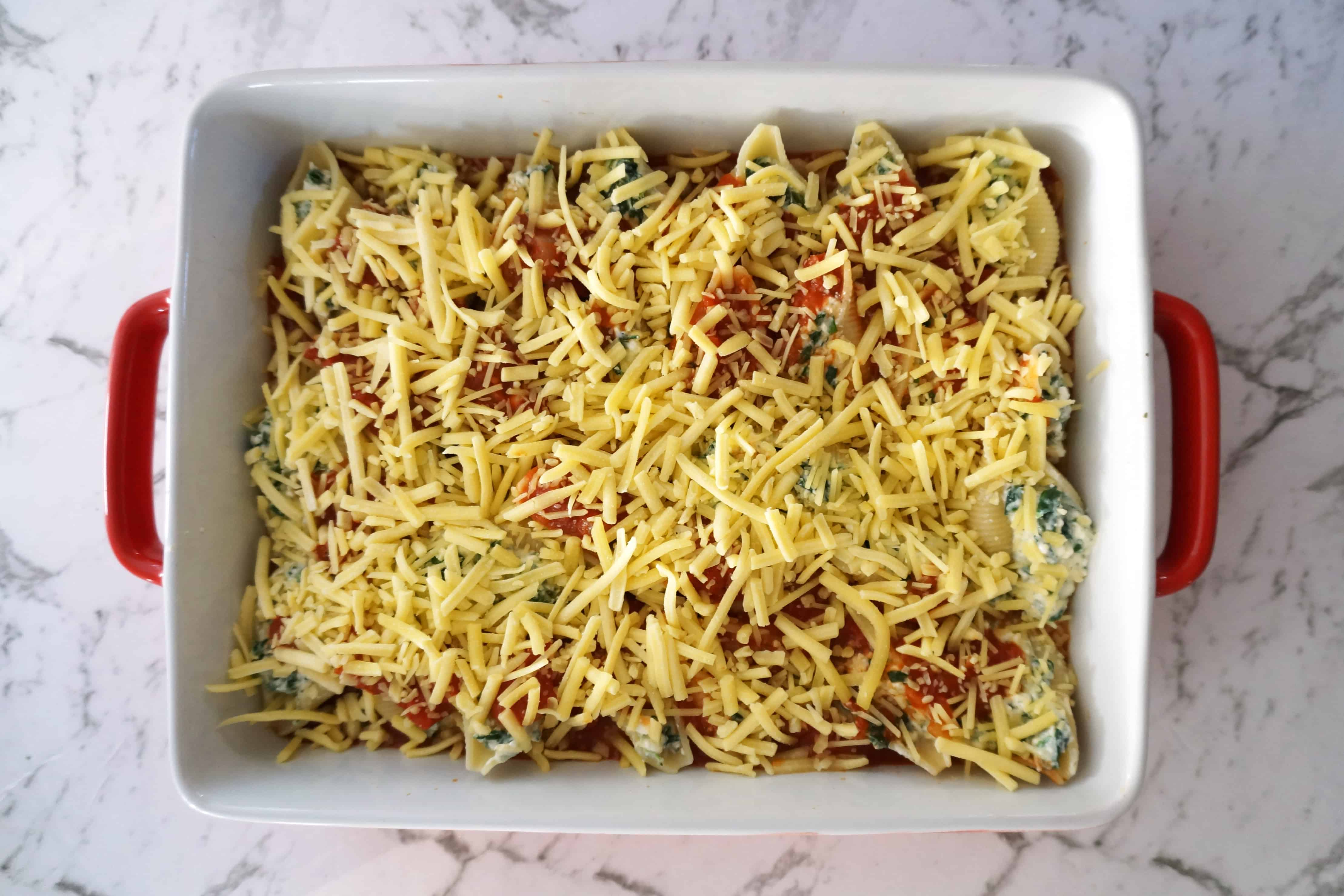 Unbaked spinach and cheese stuffed conchiglioni pasta bake in a red baking dish