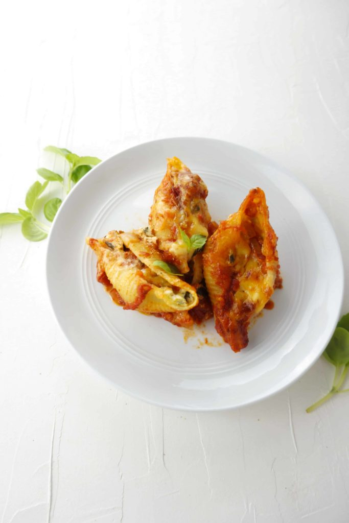 Spinach and Cheese Stuffed Conchiglioni Pasta on a white plate surrounded by fresh basil