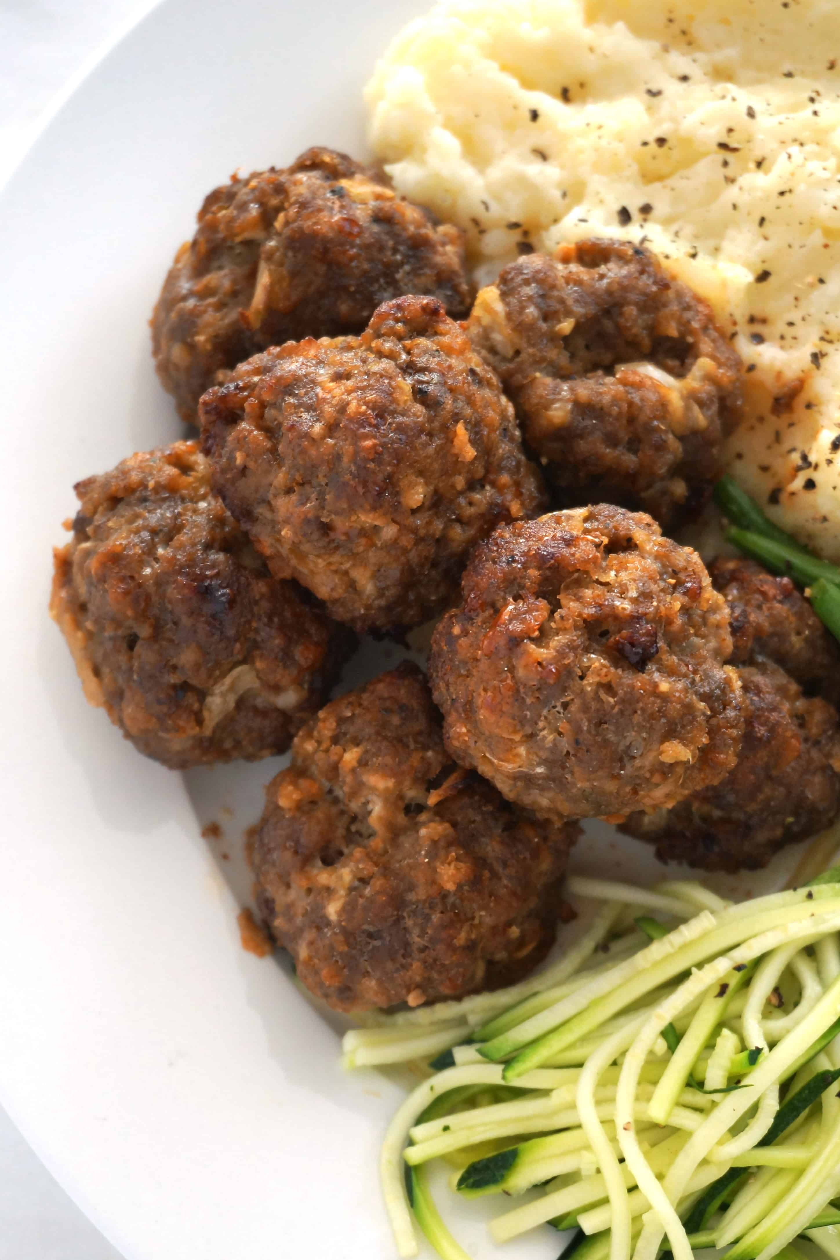 close up of baked meatballs on a plate with vegetables and mash
