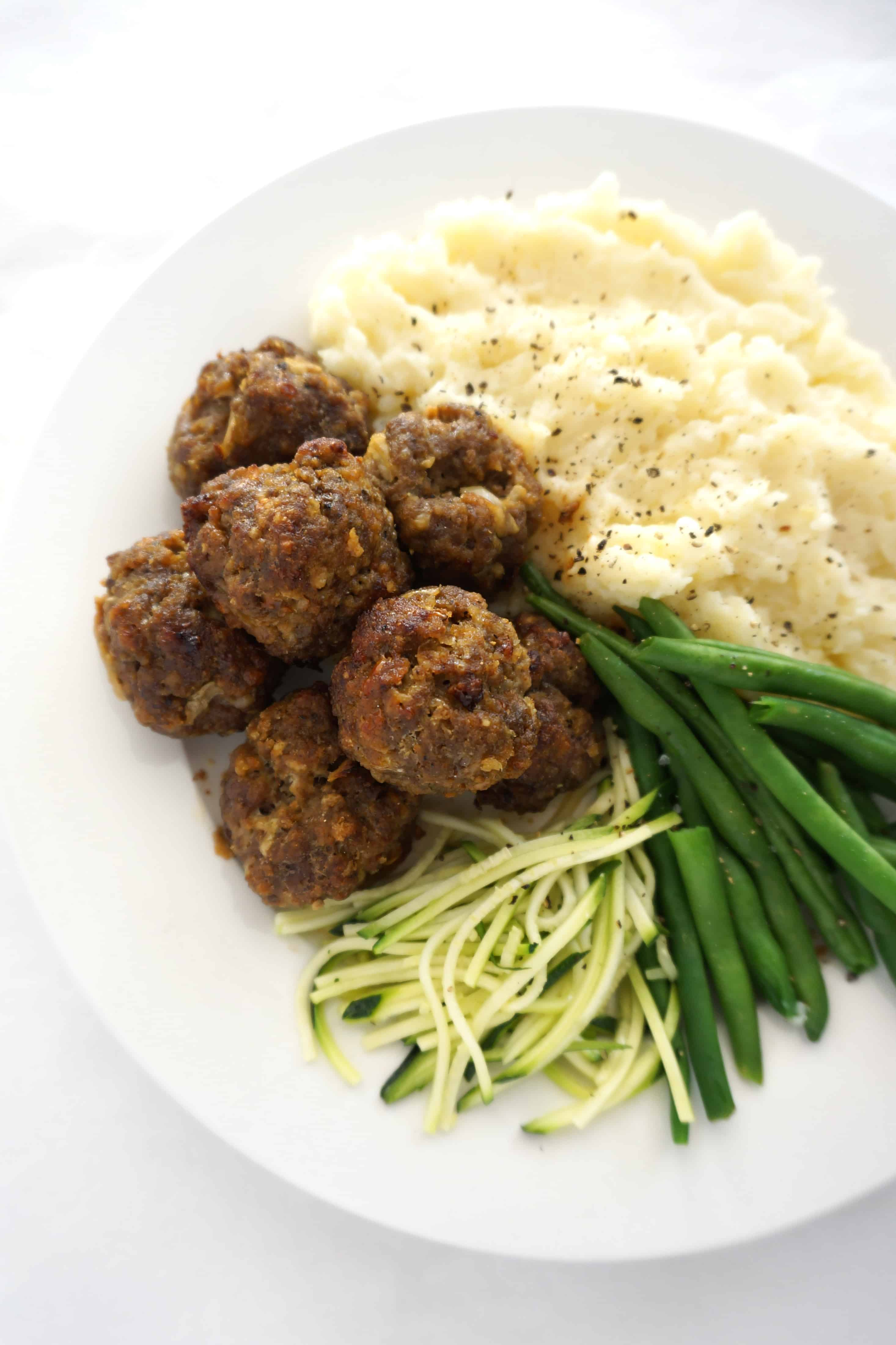 meatballs, mashed potato and vegetables on a white plate