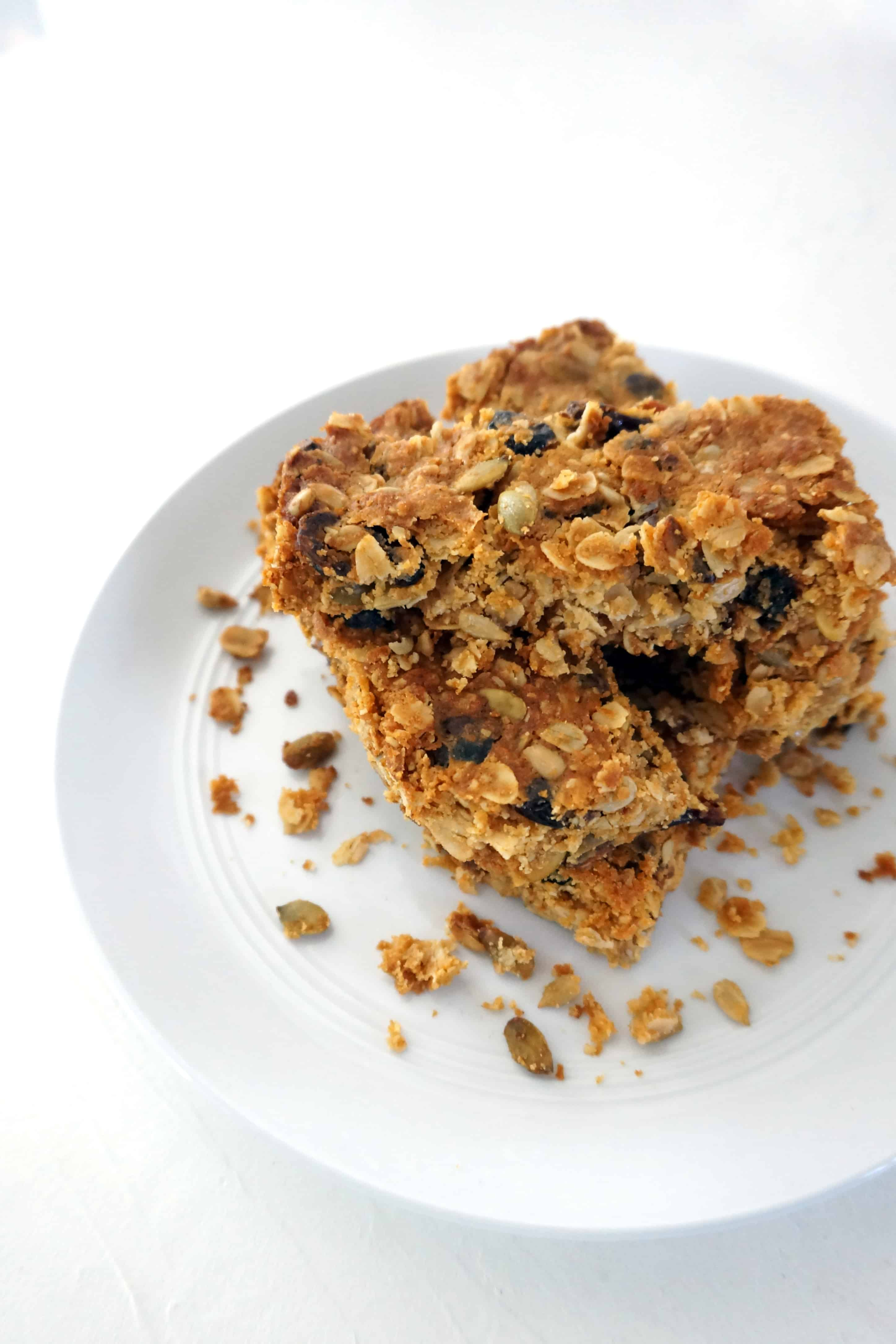 stacked muesli slice bars on a white plate