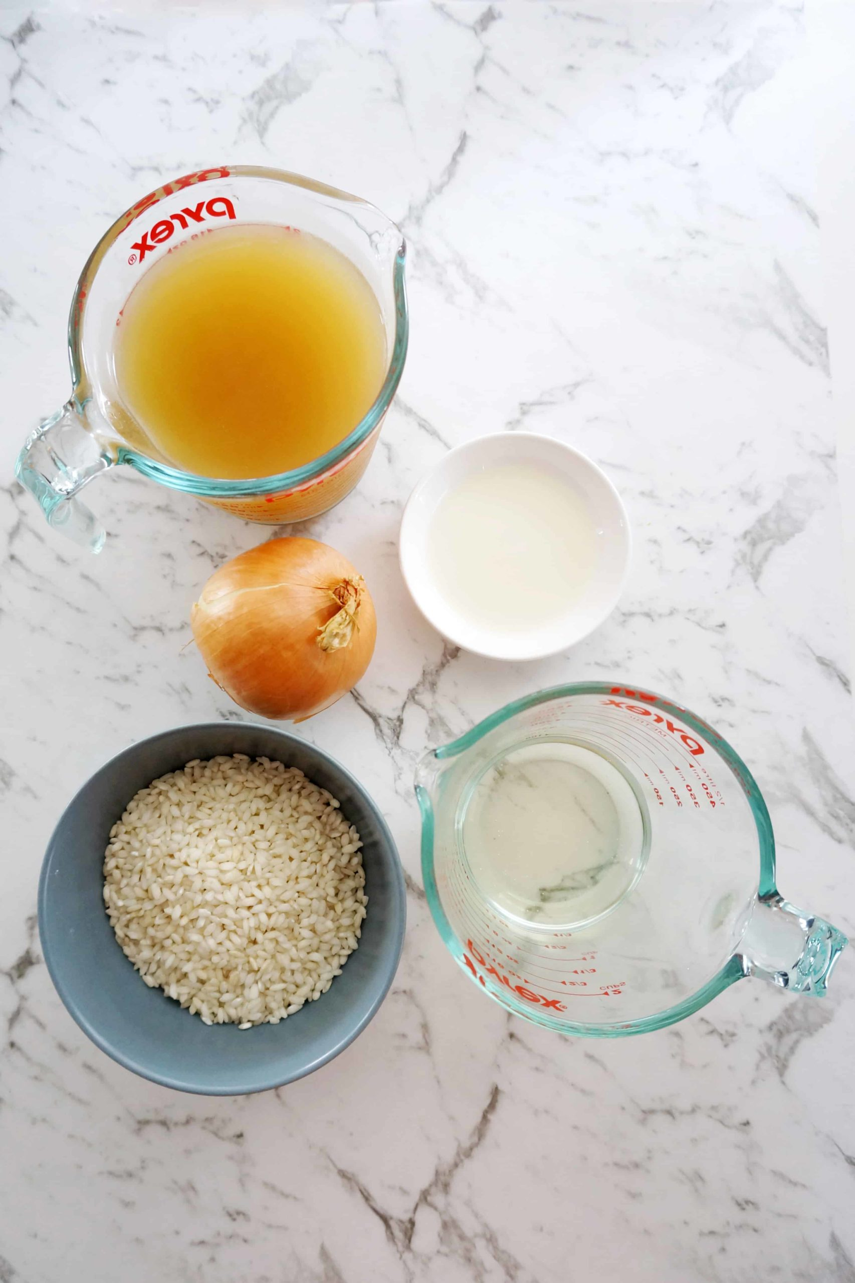 ingredients for a risotto base laid out- stock in a measuring jug, oil, an onion, arborio rice in a bowl and white win in a jug