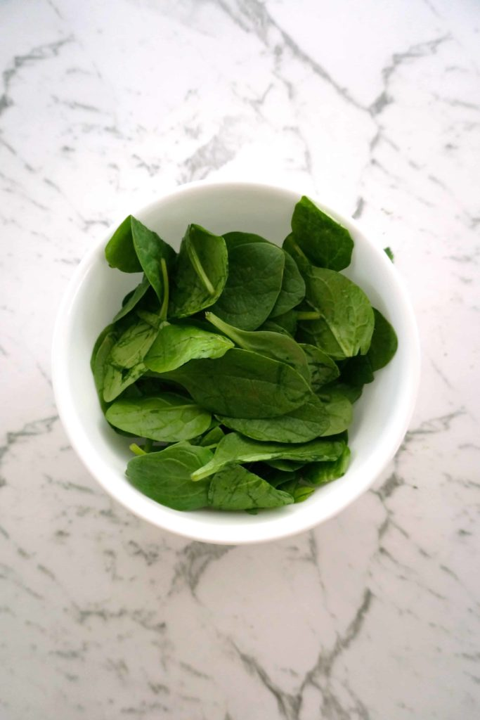 a bowl of baby spinach leaves