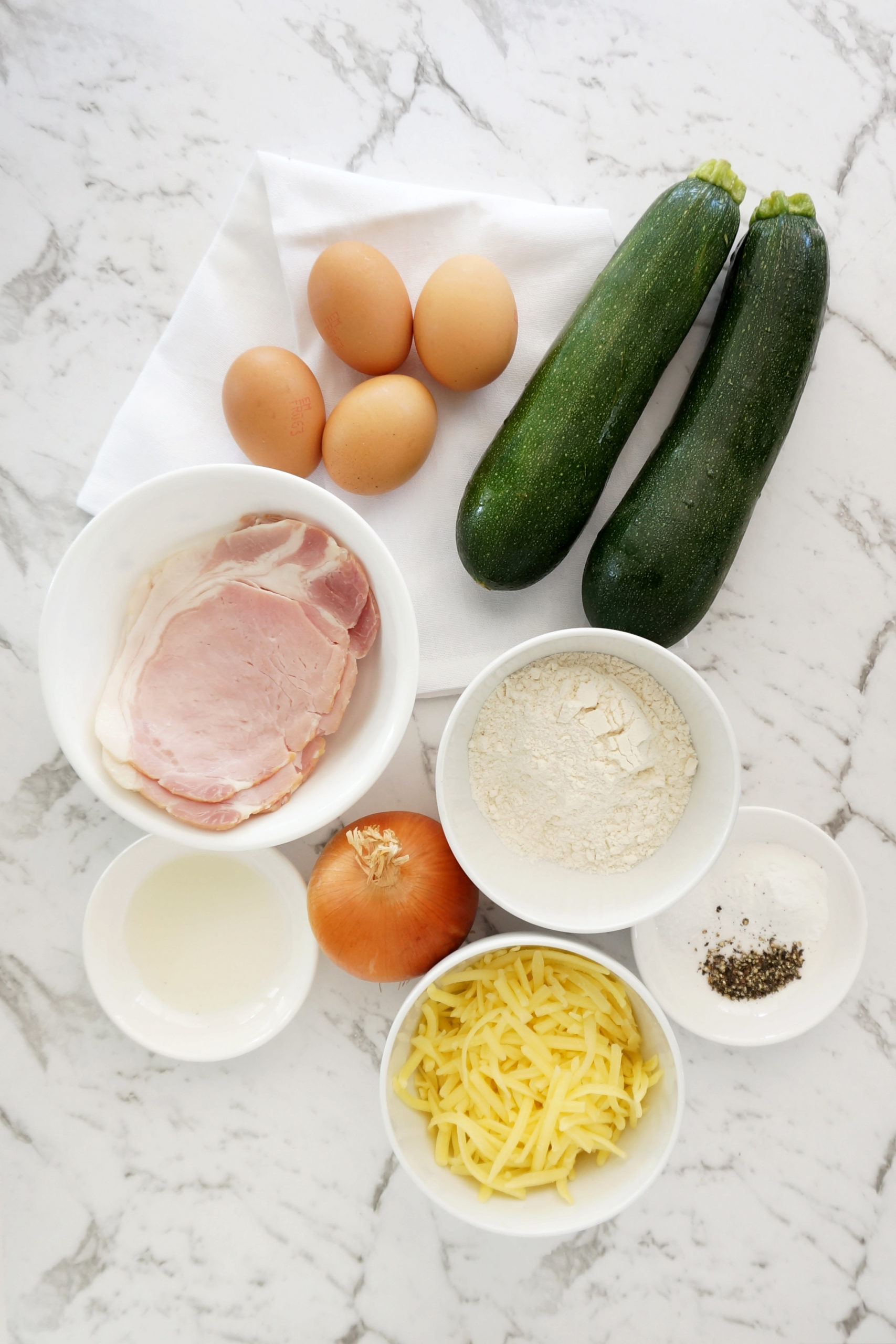 ingredients - eggs, zucchini, bacon, flour, baking powder, onion, oil, cheese, salt and pepper