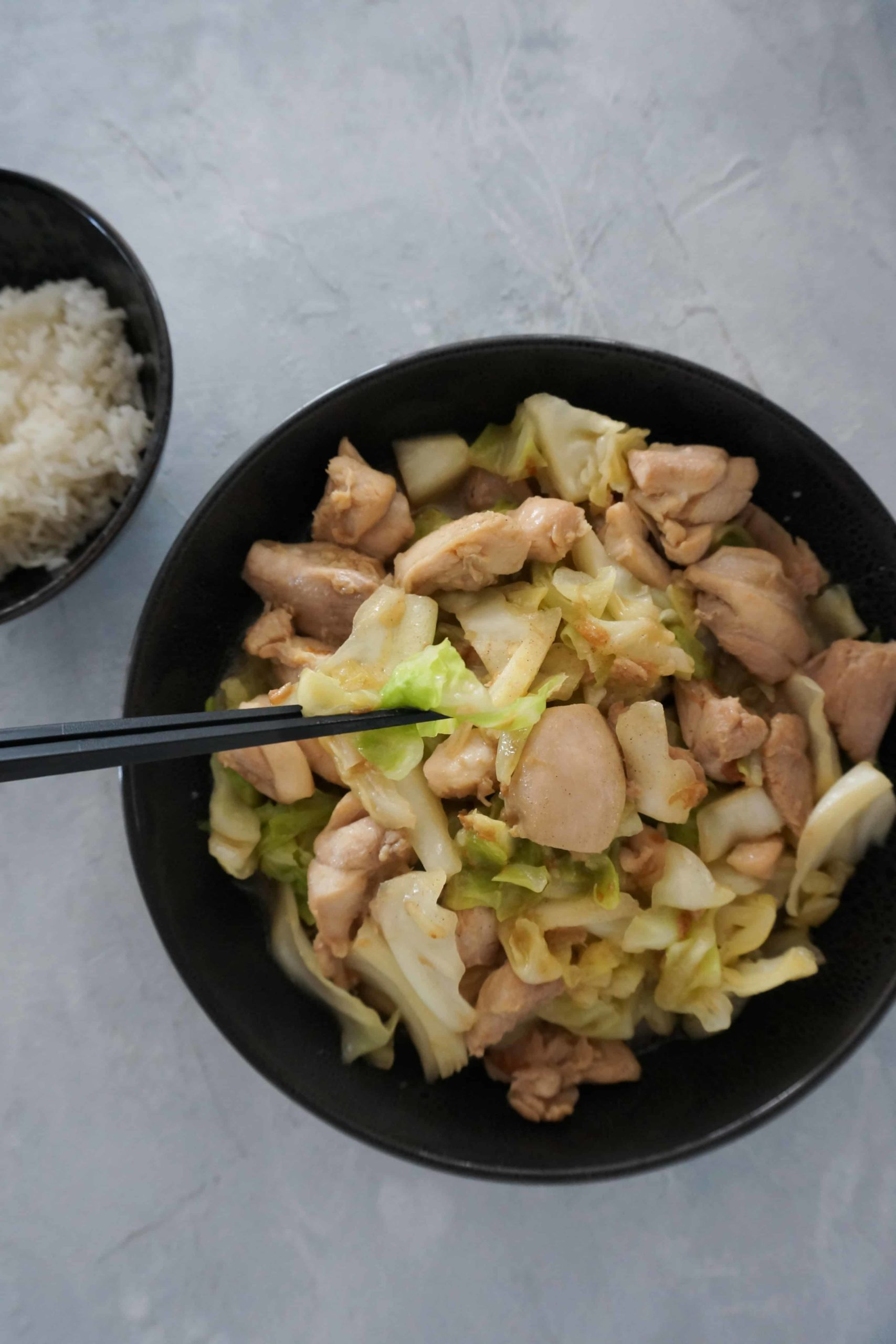 chopsticks lifting cabbage out of a plate full of chicken and cabbage stir-fry