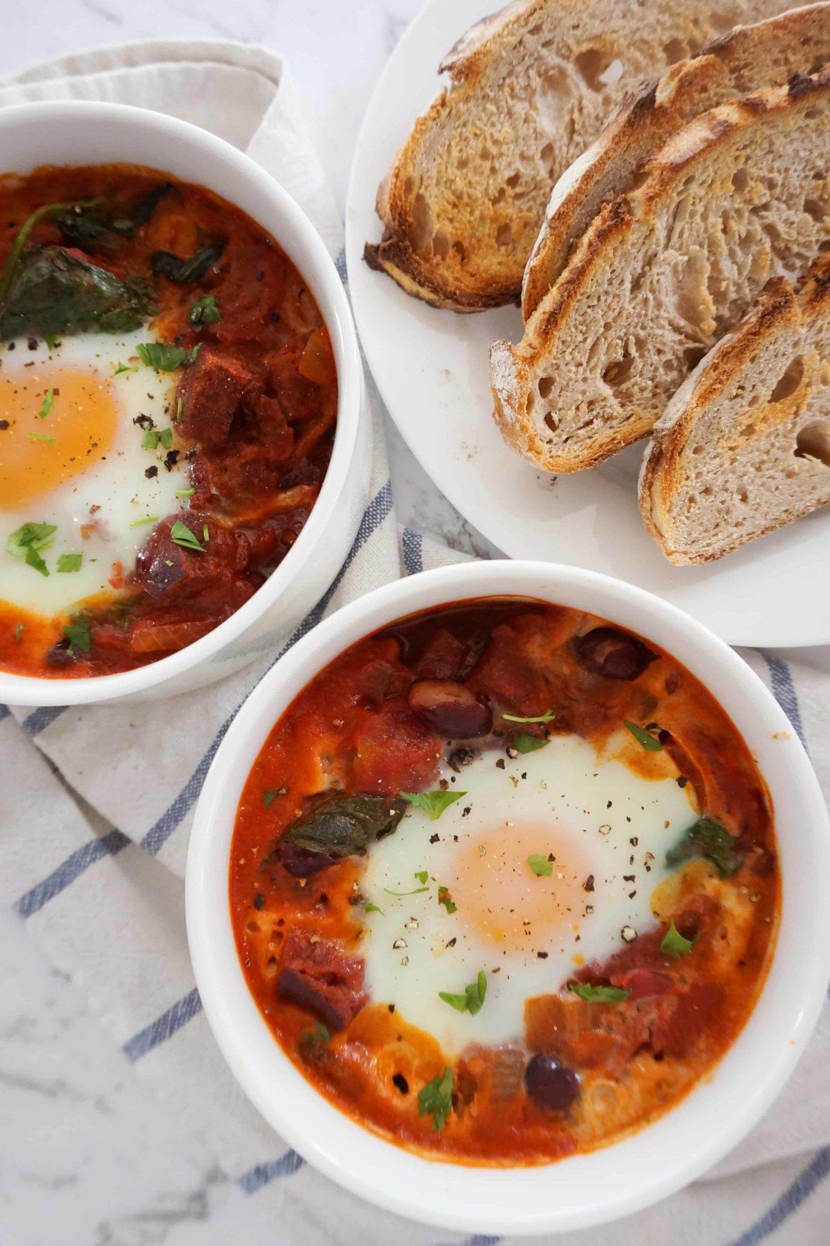 baked eggs in ramekins next to a plate of toasted bread