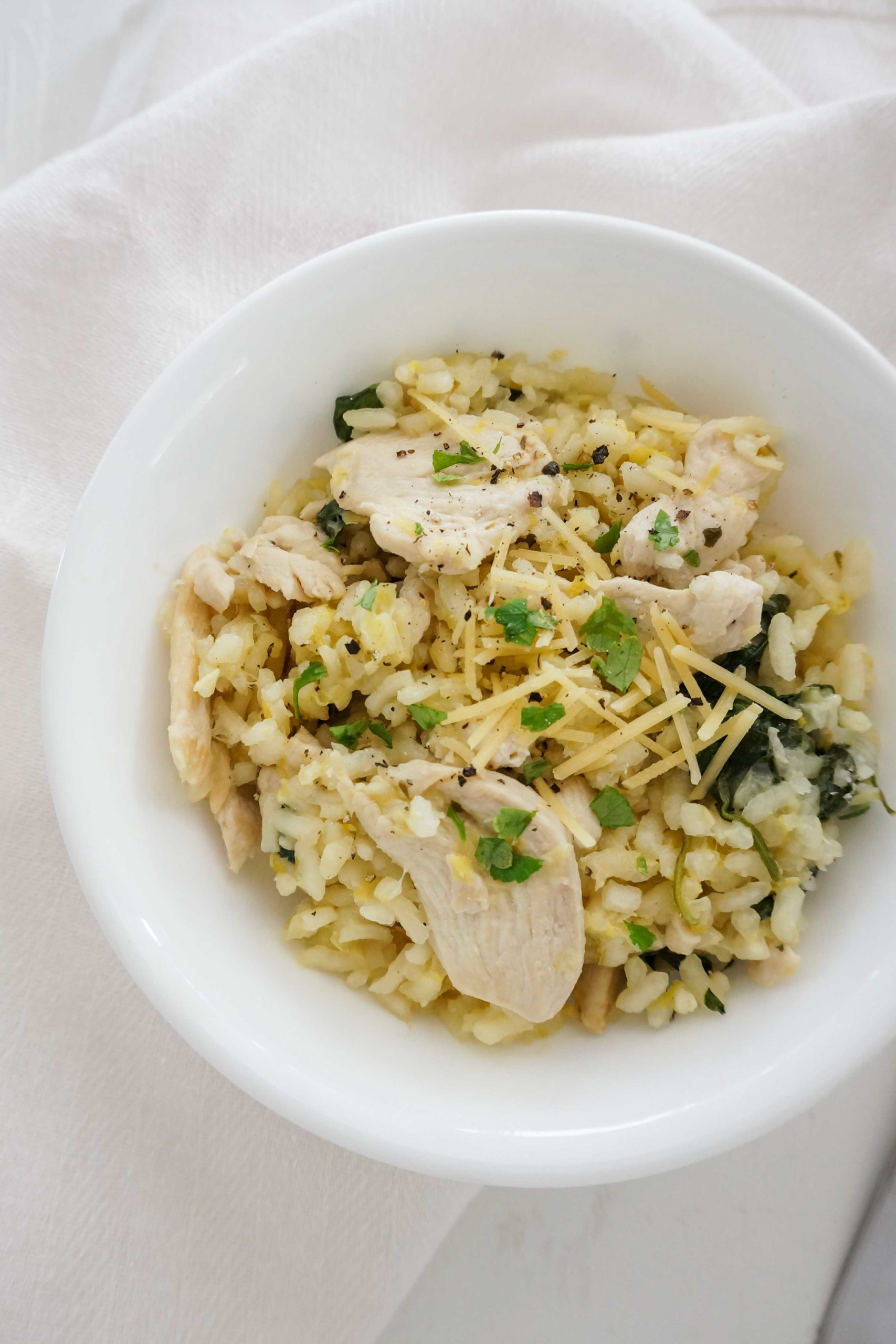 a bowl of chicken and leek risotto topped with parmesan cheese and chopped fresh parsley leaves
